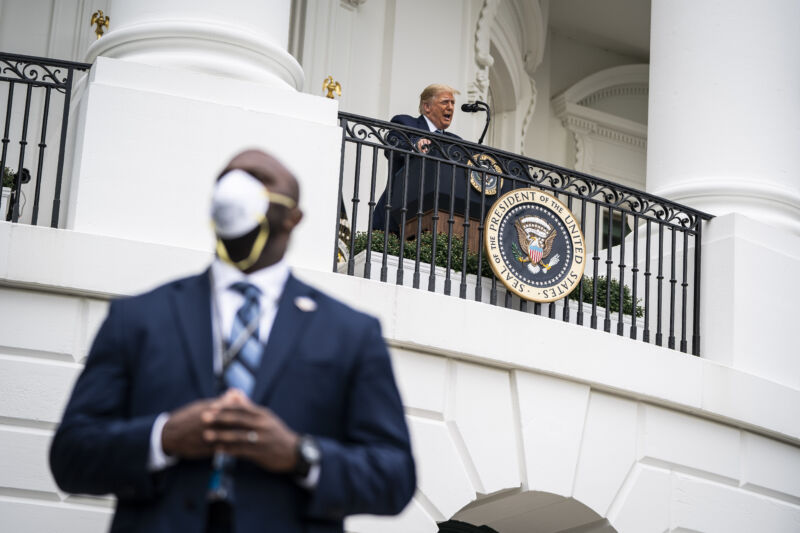A member of the United States Secret Service wearing a face mask stands guard as President Donald J. Trump speaks to supporters from the Blue Room balcony during an event at the White House on Saturday, Oct. 10, 2020 in Washington, DC.
