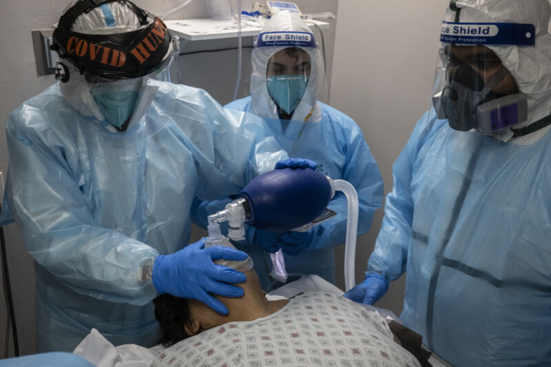 Medical workers in protective gear apply a breathing apparatus to a recline patient.
