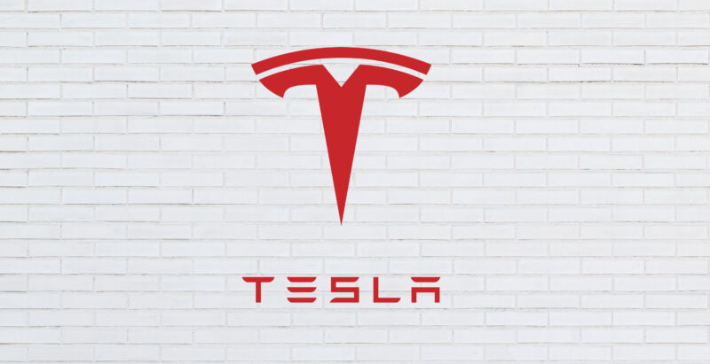 The Telsa logo superimposed on top of a white brick wall