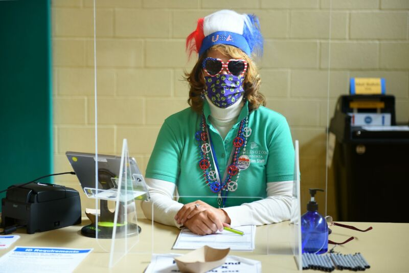 A masked woman in red, white, and blue flare sits at a desk.