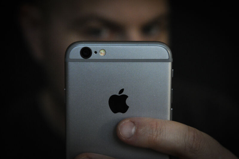 A man glowers at an iPhone, just as ad firms are worried iOS users will when they discover how they are being tracked, and that they can opt out of it.