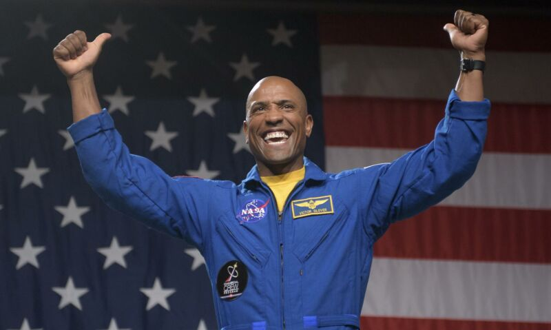 A man in a NASA jumpsuit strikes a victorious pose in front of a US flag.