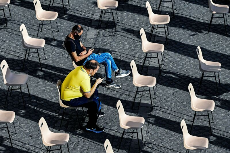 Several rows of outdoor seating are empty, save two men staring at their smartphones.