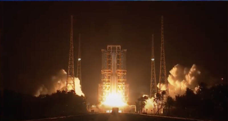Image of a rocket with engines igniting on the launch pad.