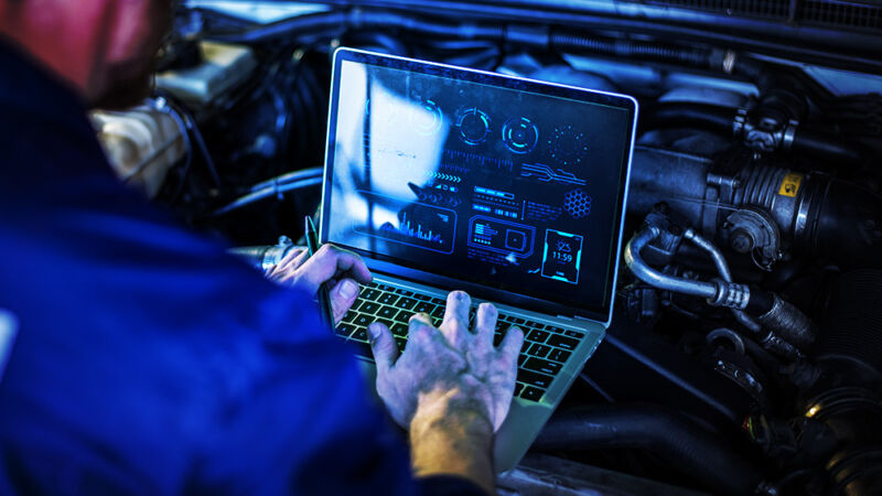 A man operates a notebook computer over the open engine of a car.