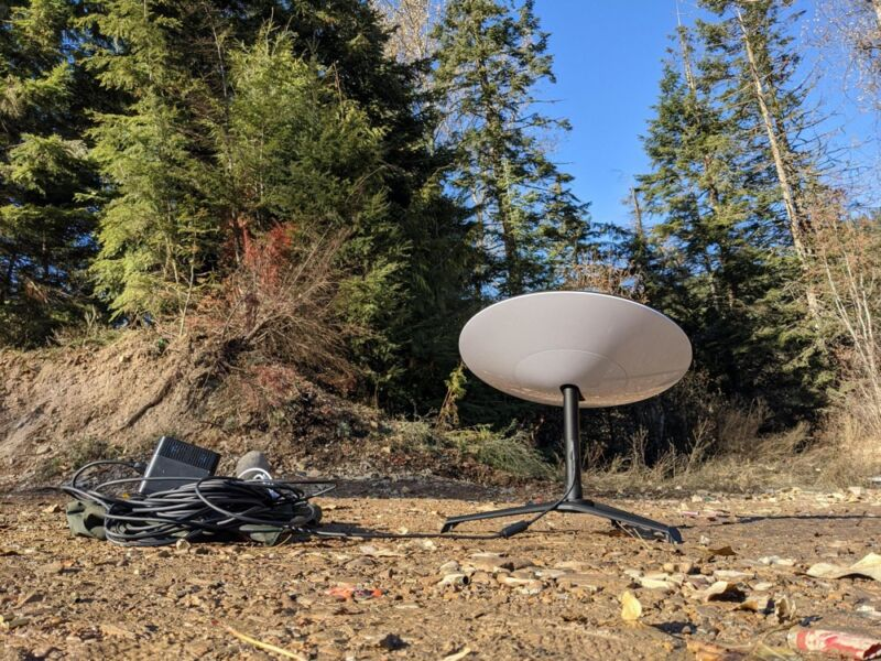 A SpaceX Starlink satellite dish placed on the ground in a forest clearing.