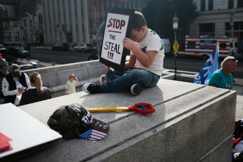 HARRISBURG, PENNSYLVANIA - NOVEMBER 05: A child holds a sign as dozens of people calling for stopping the vote count in Pennsylvania due to alleged fraud against President Donald Trump gather on the steps of the State Capital on November 05, 2020 in Harrisburg, Pennsylvania. The activists, many with flags and signs for Trump, have made allegations that votes are being stolen from the president as the race in Pennsylvania continues to tighten in Joe Biden's favor.
