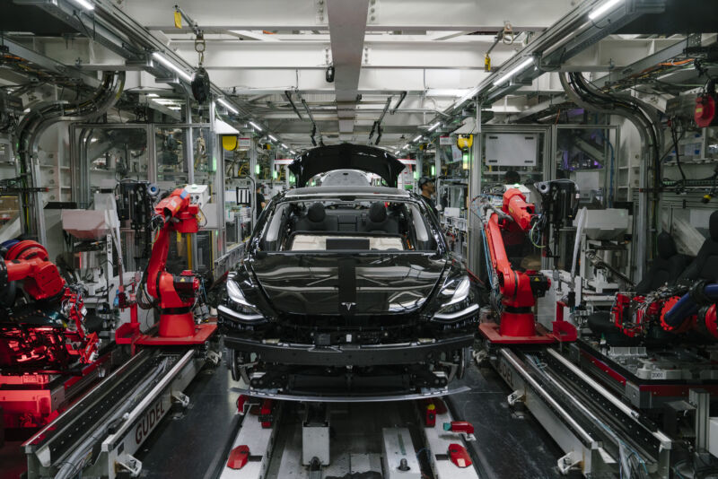 Robotic arms surround an incomplete sedan.