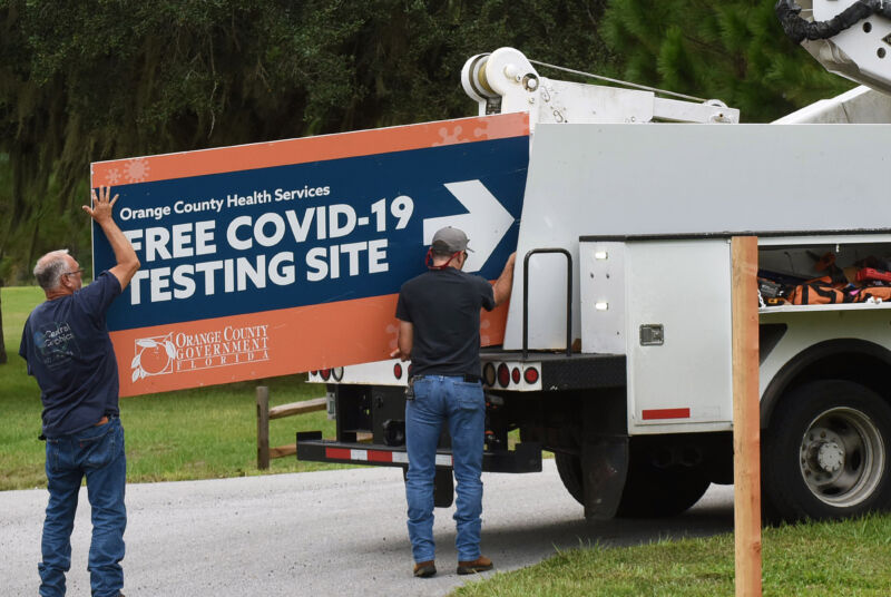 Workers removing a sign from a drive-through COVID-19 testing site in Orlando, Florida, in October 2020.