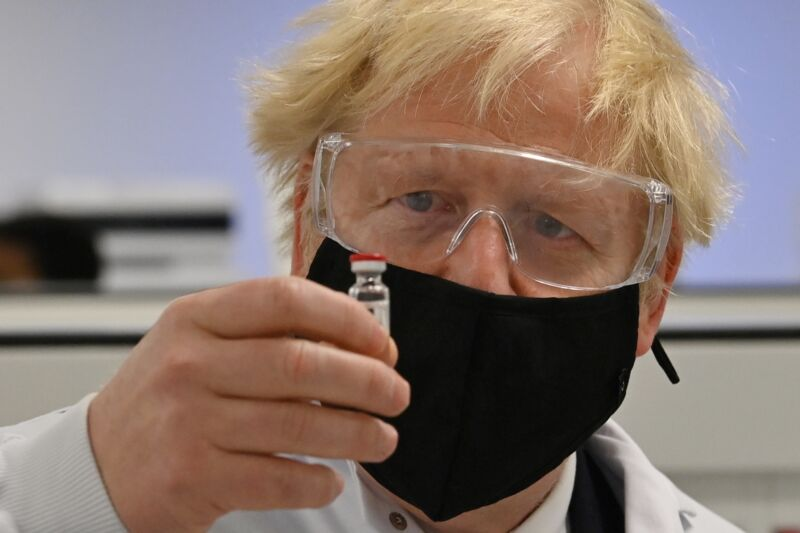 A man with a face mask, goggles, and tousled hair examines a small vial.