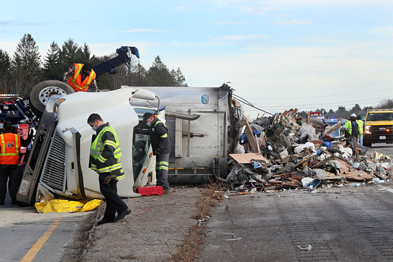 Technology Road workers attend to an overturned semi truck.
