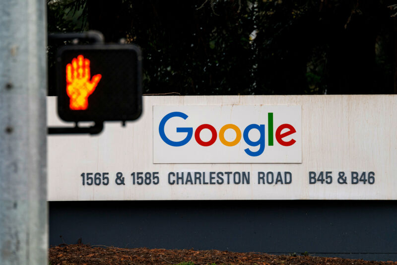 A traffic signal in front of Google HQ indicates that pedestrians should not walk.
