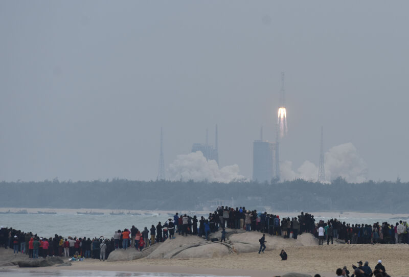 A body of water separates crowds from a rocket launch.