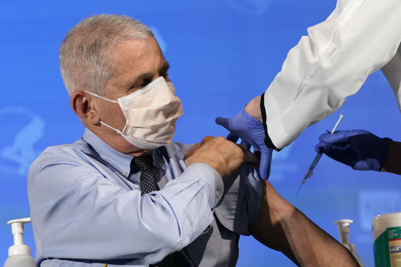 A masked man rolls up his sleeve to receive an injection.