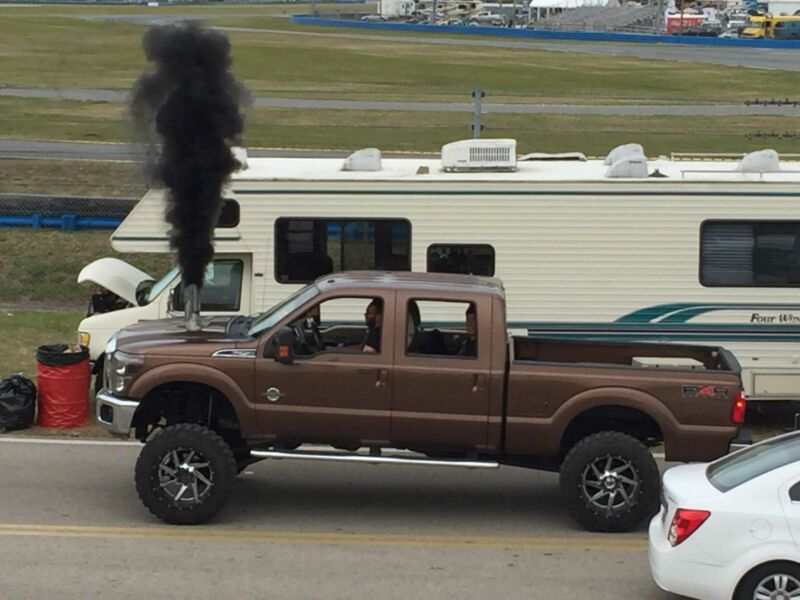 A pickup truck emits a huge black cloud of soot from an exhaust cut into its hood.