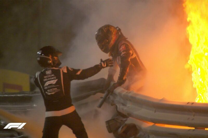 A racing driver is helped away from a fiery crash