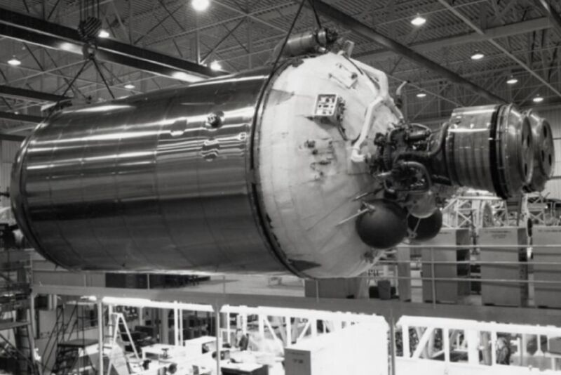 Black-and-white photo of a huge rocket component in a giant hangar.