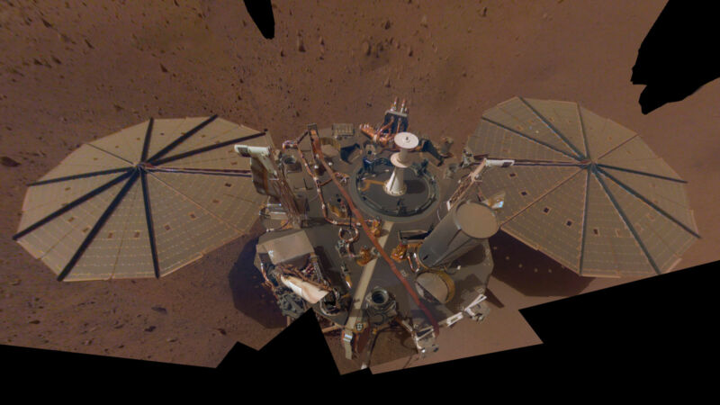 Image of the lander hardware flanked by two arrays of solar panels.