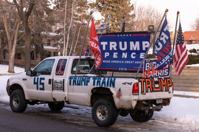 A white pickup truck is decorated in pro-Trump paraphernalia.