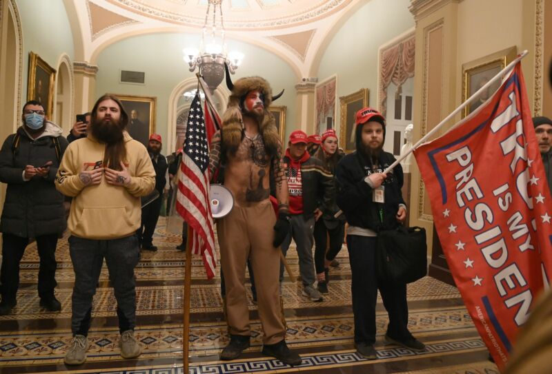 Men with flags and bizarre costumes pose for a photo in a neoclassical corridor.
