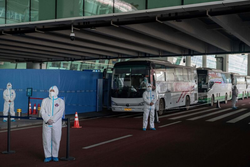 Health workers in personal protection suits stand next to buses at a cordoned-off section of the international airport in Wuhan on January 14, 2021, following the arrival of a World Health Organization (WHO) team investigating the origins of the COVID-19 pandemic.