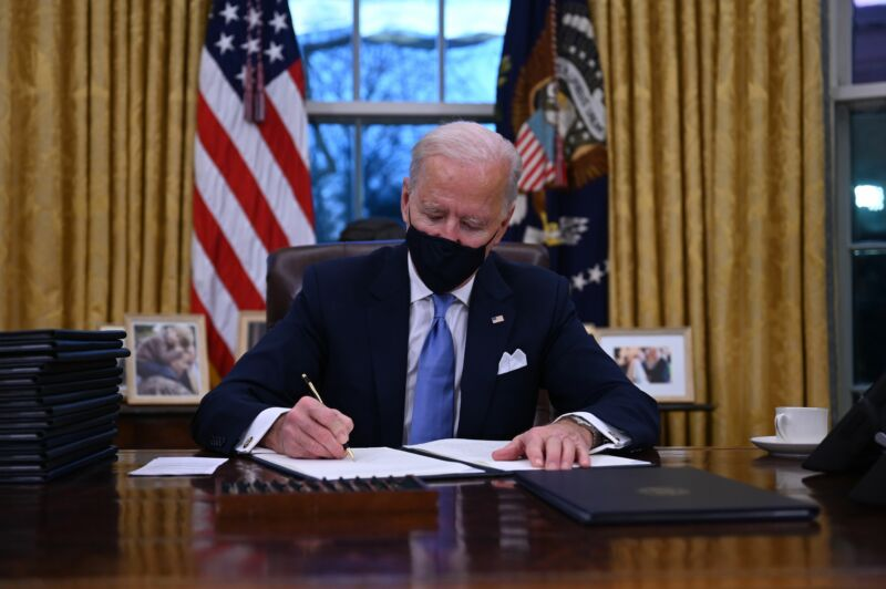 US President Joe Biden sits in the Oval Office as he signs a series of orders at the White House in Washington, DC, after being sworn in at the US Capitol on January 20, 2021.