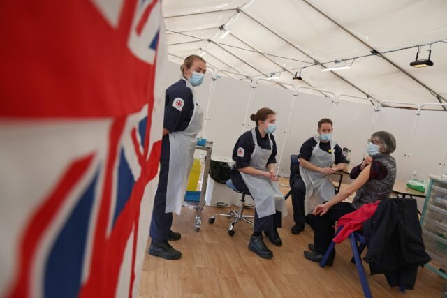 A patient prepares to receive an injection of the Oxford/AstraZeneca COVID-19 vaccine by Royal Navy medics at a vaccination center set up at Bath racecourse in Bath, southwest England.