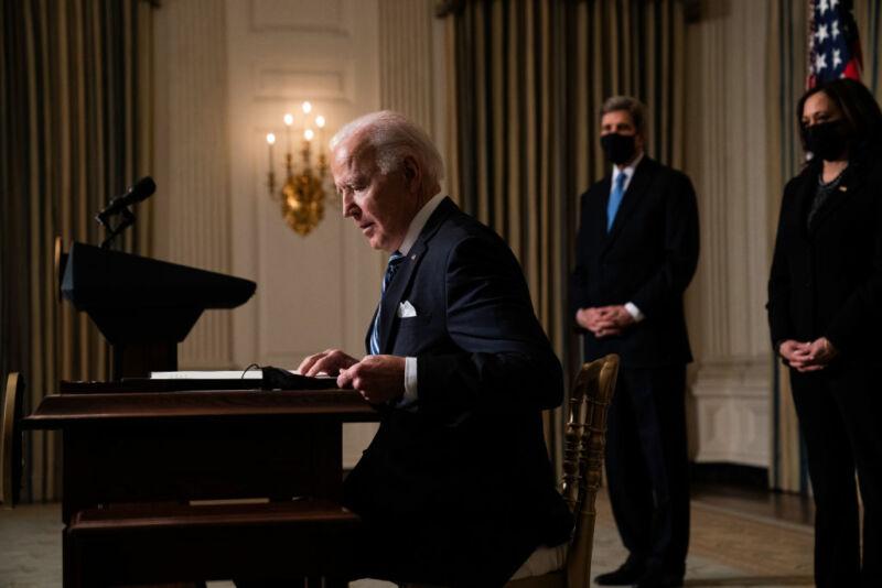 تصویری از یک مرد که پشت میز نشسته است و یک زن و مرد پشت سر او ایستاده اند.