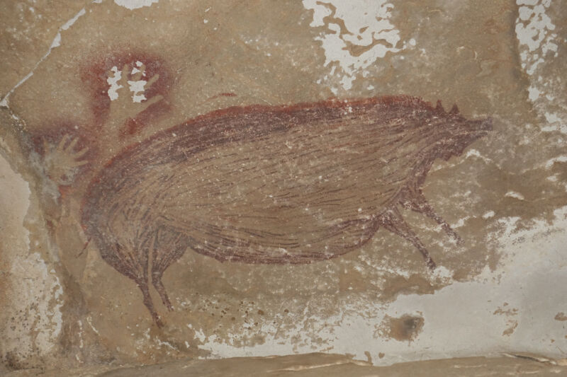 Color photo of stylized pig painted in red on a rock wall