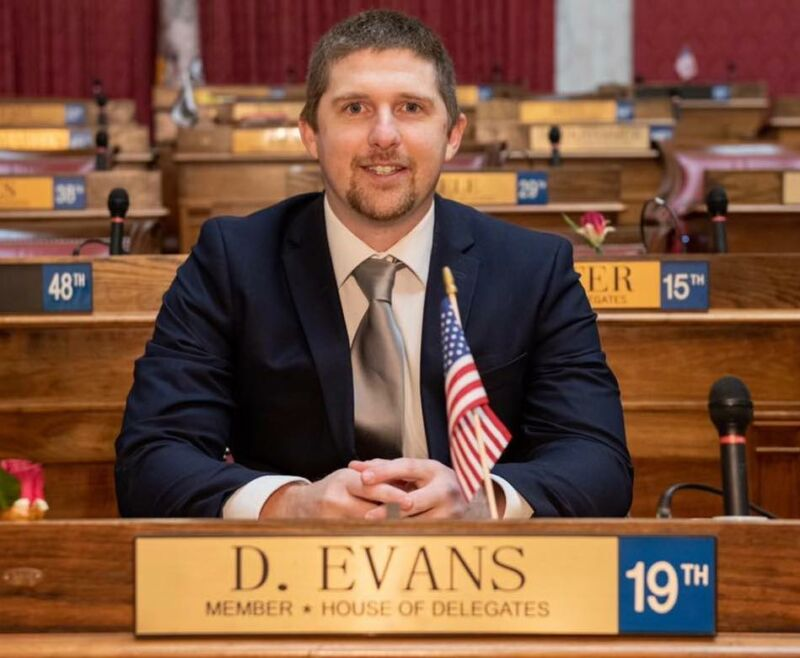 Derrick Evans sitting in the West Virginia House of Delegates, with a small American flag propped up in front of him.
