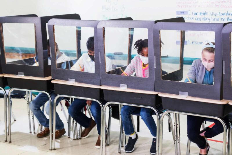Masked school children work at desks separated by clear barriers.