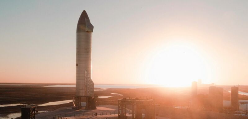 A rocket sits on a launchpad as the Sun blazes on the horizon.