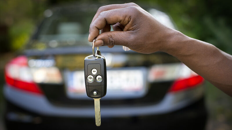 Stock photo of a dark-skinned hand holding out a set of car keys.