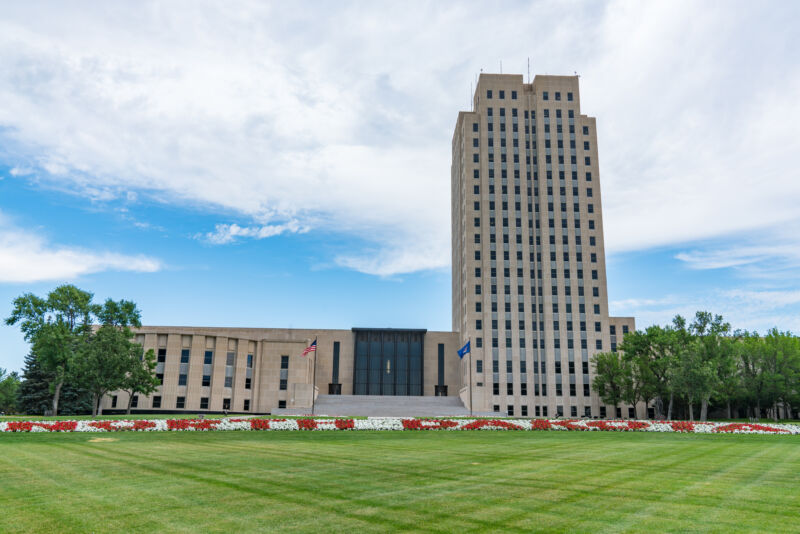 A wide lawn surrounds a 21-story Art Deco tower.