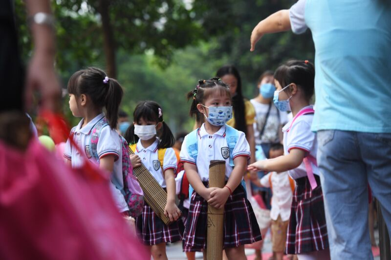Masked girls in matching uniforms wait for school to begin.