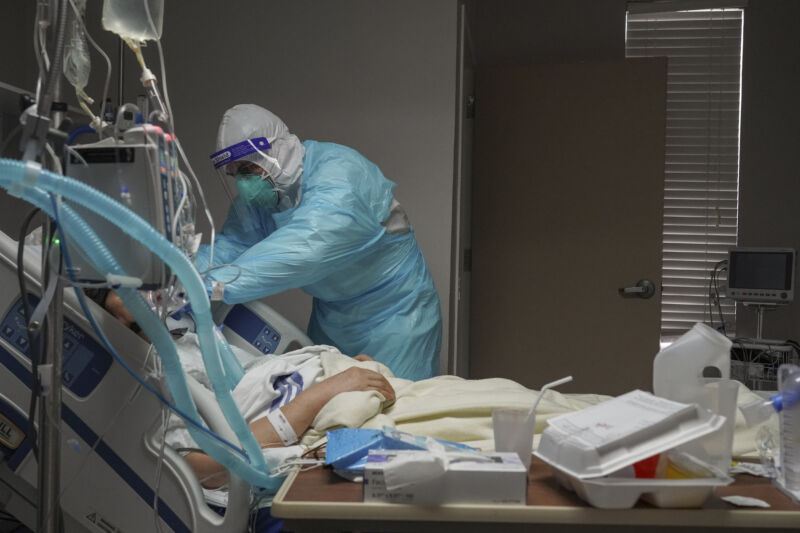 A medical staff member adjusts a ventilator on a patient in the COVID-19 intensive care unit (ICU) at the United Memorial Medical Center on December 2, 2020 in Houston, Texas.
