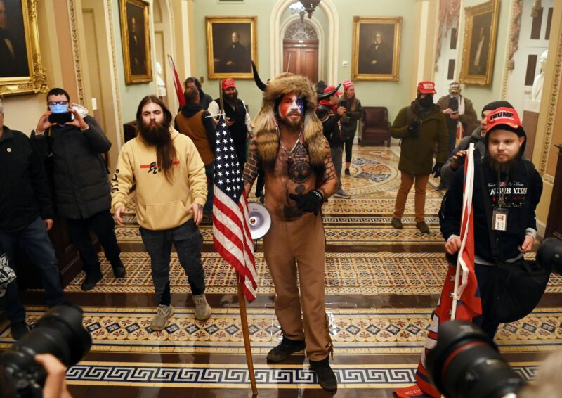 Supporters of former President Donald Trump, including Jake Angeli, a QAnon supporter known for his painted face and horned hat, enter the US Capitol on January 6.