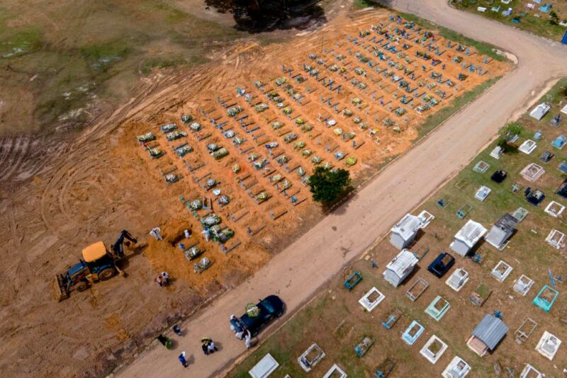 Image of an orange dirt lot with a tractor digging near the edge of a grid of individual coffins.