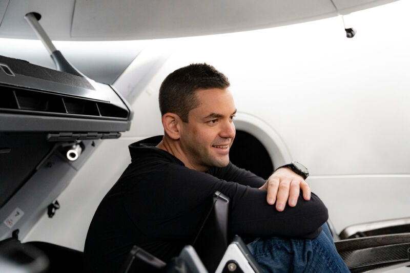 A young man smiles while sitting amidst machinery.