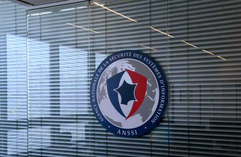 An agency logo hangs on an interior office window.