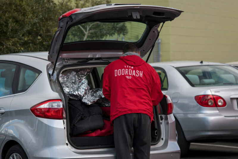 A DoorDash Inc. delivery person arranges an order in the back of a vehicle outside of a DoorDash Kitchens location in Redwood City, California.