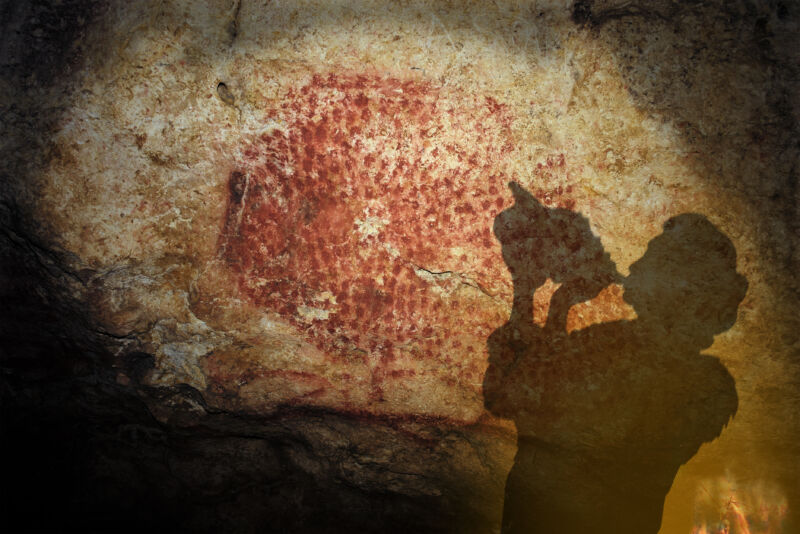 Color photo of a person with a conch shell raised to their mouth, silhouetted against a red-painted cave wall.