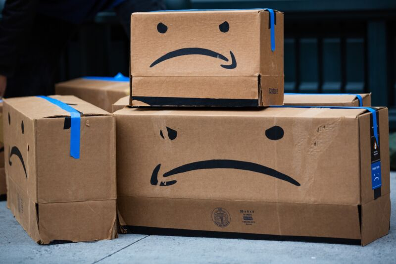 Cardboard boxes made to resemble Amazon packages, but with the logo in the shape of a frown.