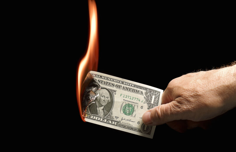 A one-dollar bill set on fire.