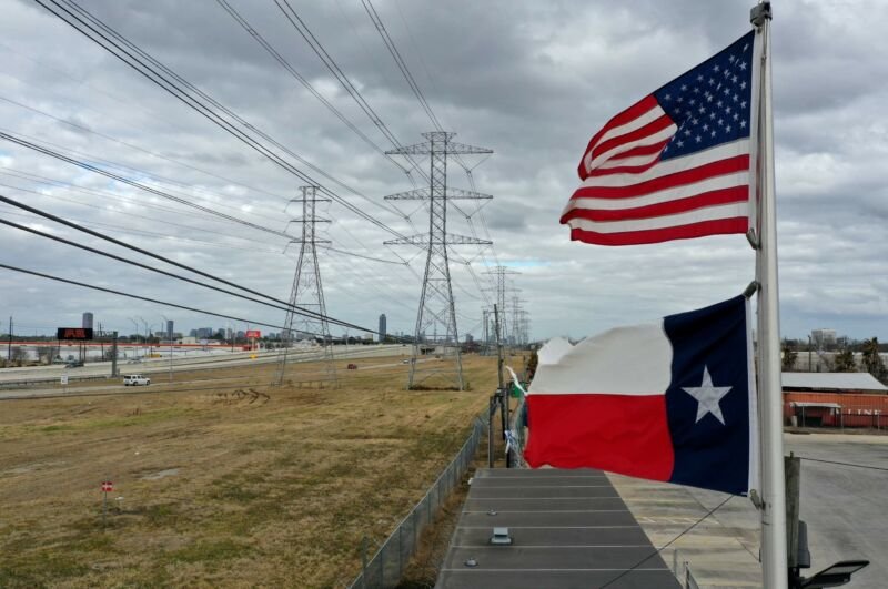 US and Texas flags seen next to power lines and transmission towers.