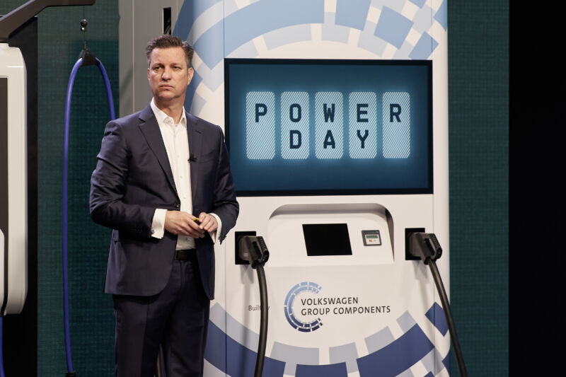 A man in an open-collared suit stands in front of a large power charger mockup.