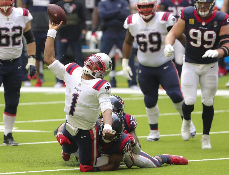 HOUSTON, TX - NOVEMBER 22: New England Patriots quarterback Cam Newton desperately throws an incomplete pass as Houston Texans Justin Reid sacks him during fourth quarter NFL action.