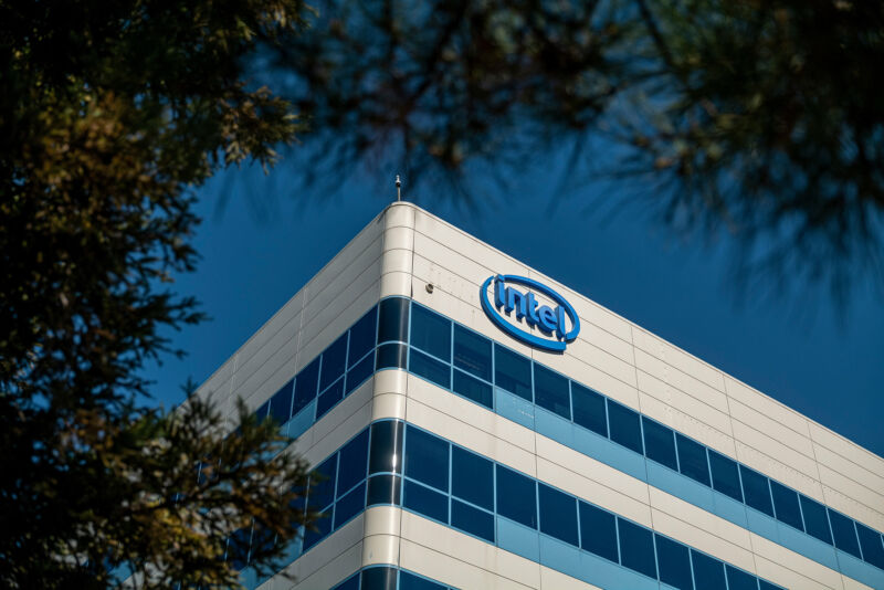 A multistory building with an Intel logo on the wall of its top floor.