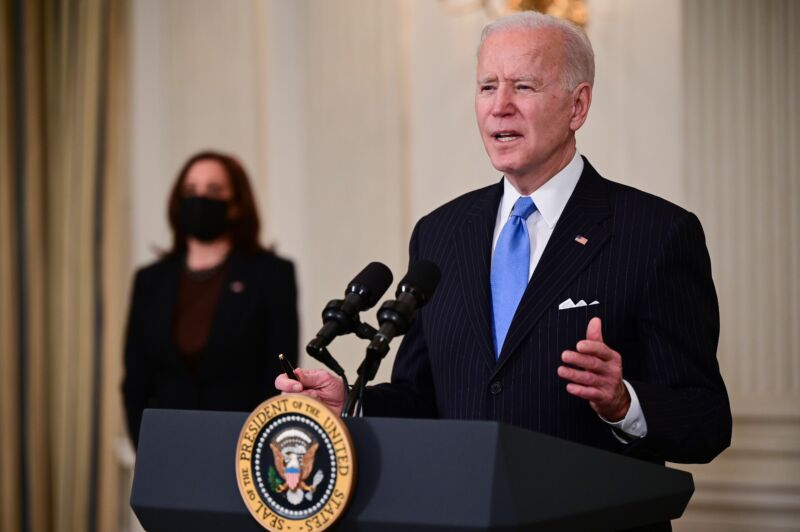 An older man in a suit speaks at a podium with a presidential seal.