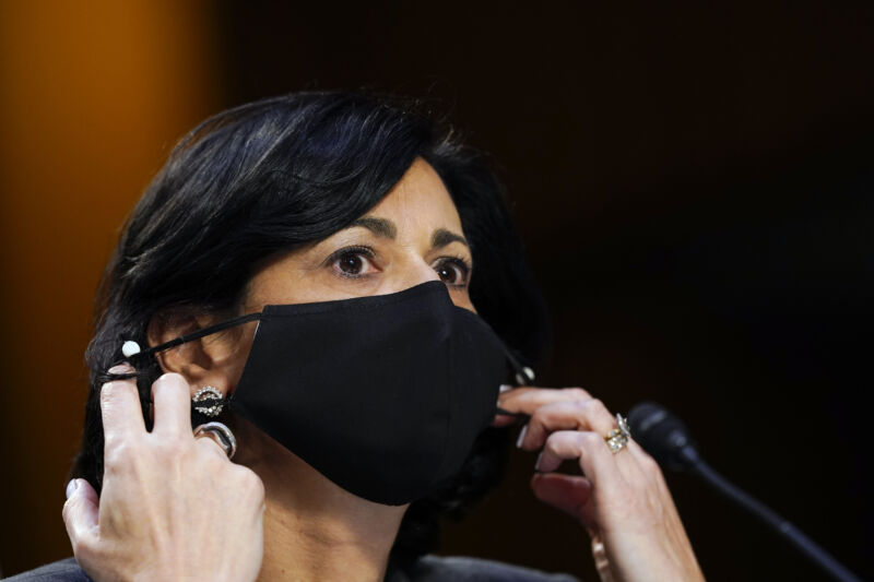 A woman adjusts her face mask while sitting in front of a microphone.